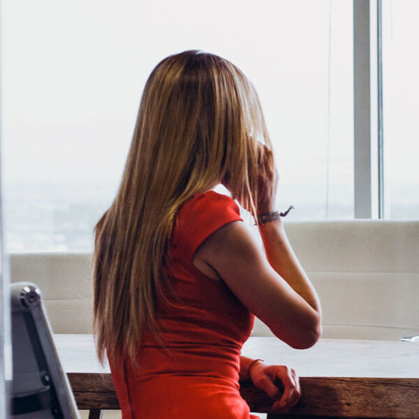 Frau sitzt an einem Konferenztisch und telefoniert