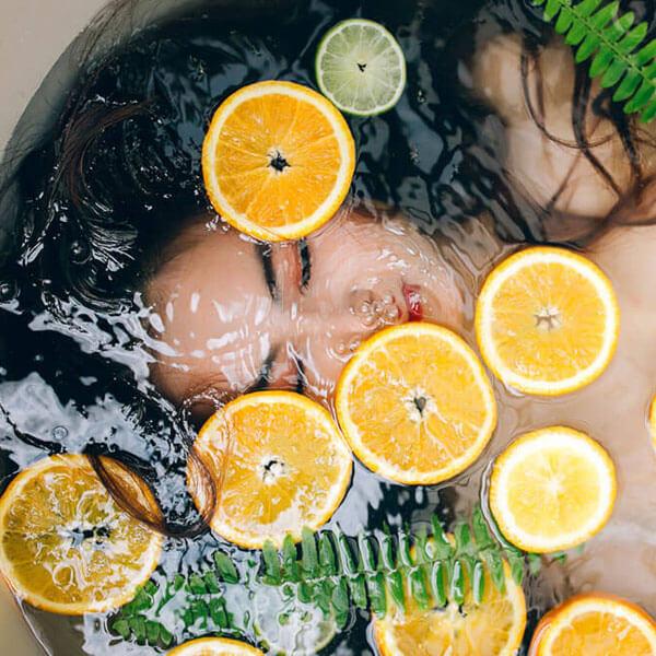 Spa, Frau in Badewanne, Kopf unter Wasser, Orangenscheiben, Farn