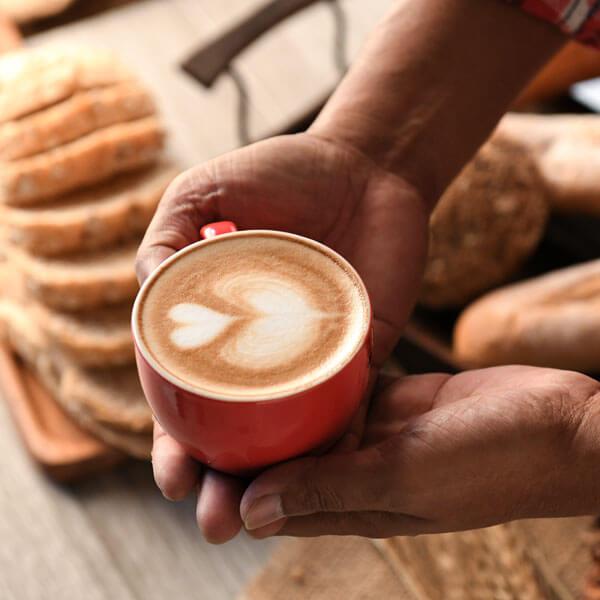 Barrista, italienischer Kaffee mit Herz wird mit beiden Händen gegeben